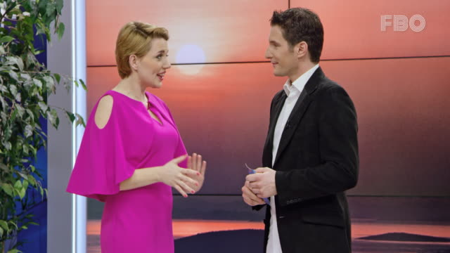 Male live talk show host welcoming his female celebrity guest on the show