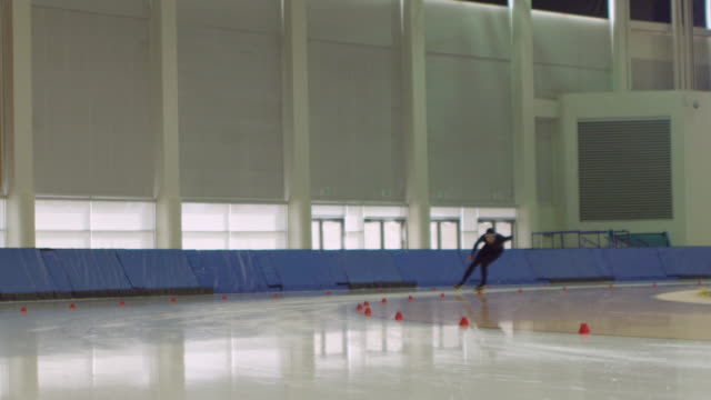 ms slo mo male long track speed skater practicing on ice in arena - アイススケート点の映像素材/bロール