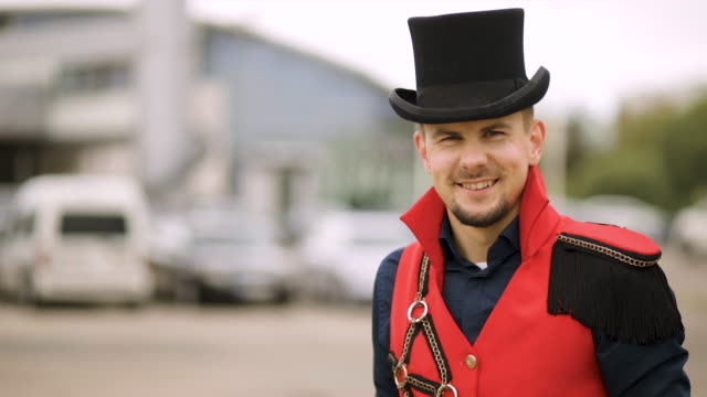 male magician entertainer in black top hat and red stage costume turns around and looks at camera - top hat stock videos & royalty-free footage