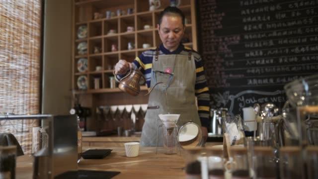 vídeos de stock, filmes e b-roll de fazer café no laboratório do café de macho - só um homem maduro