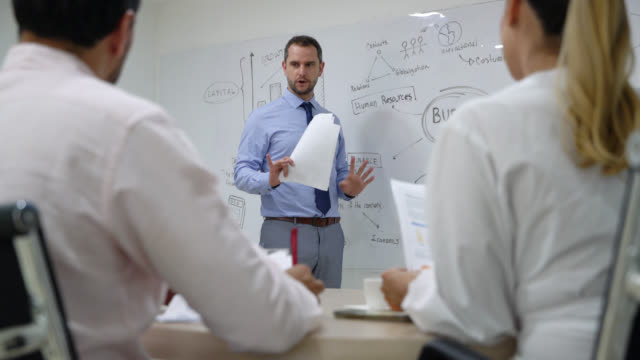 male manager at the office training his team pointing at white board while talking - business strategy stock videos & royalty-free footage