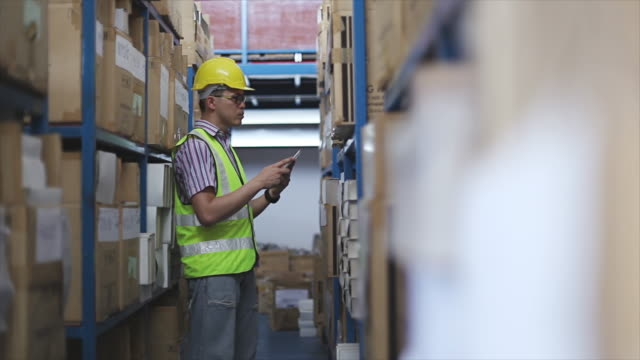 Male manager using tablet in a warehouse