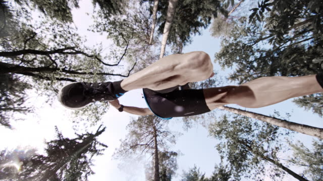 SLO MO manliga marathon konkurrent att göra ett hopp i skogen