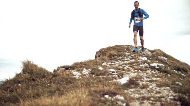 slo mo male marathon runner descending the mountain on a gravel trail across the grassy ridge - cross country running stock videos & royalty-free footage