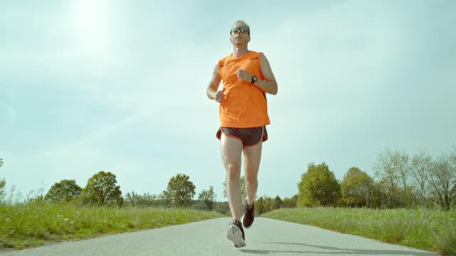 slo mo ts 雄マラソンランナーのランニングの田園地帯 - サングラス点の映像素材/bロール