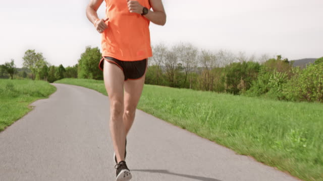 slo mo ts male marathon runner running on a sunny day - one mid adult man only stock videos & royalty-free footage