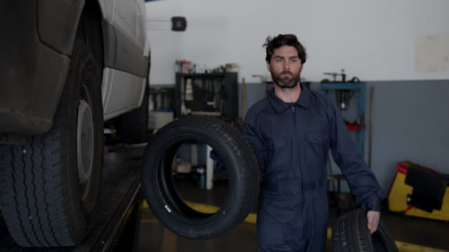 male mechanic carrying tires at an auto repair shop - wheel stock videos & royalty-free footage