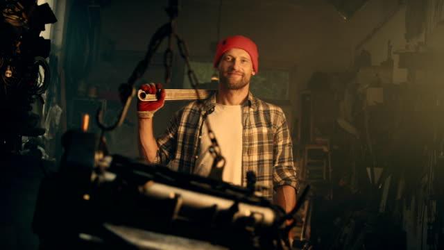 männliche mechaniker in der werkstatt mit großen hammer - mechaniker stock-videos und b-roll-filmmaterial