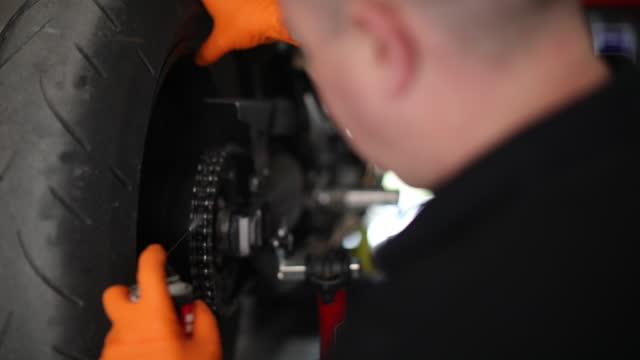 vídeos y material grabado en eventos de stock de mecánico masculino reparando cadena de motocicletas - reparar