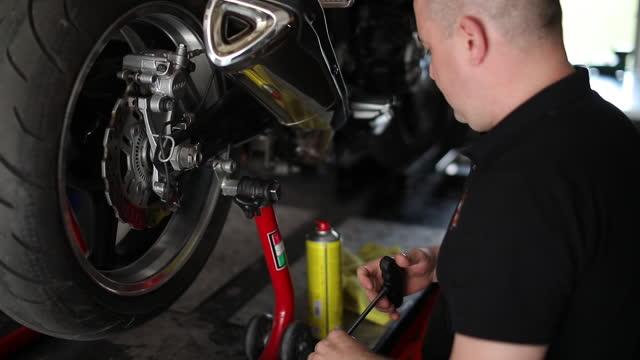 male mechanic repairing motorcycle - repairing stock videos & royalty-free footage