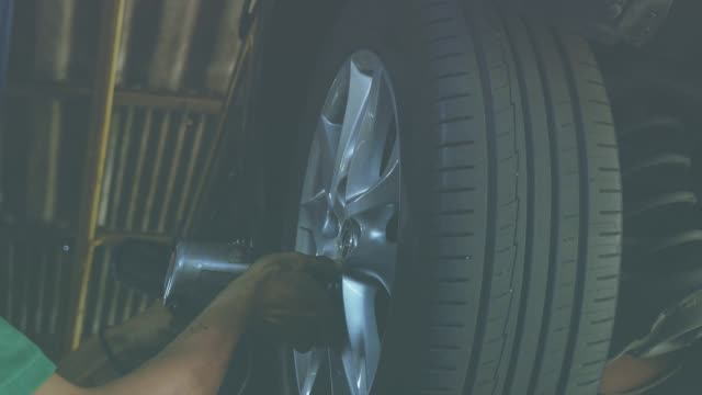 vídeos de stock e filmes b-roll de slo mo: male mechanic replace chock up of undercarriage vehicle or automobile. - chassi