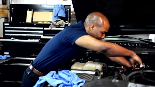 male mechanic working in auto repair shop. - car engine stock videos & royalty-free footage