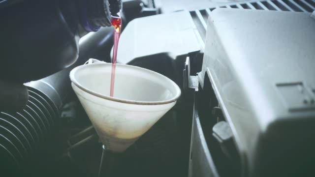 vídeos de stock, filmes e b-roll de mecânico masculino, trabalhando na oficina mecânica. - óleo de motor