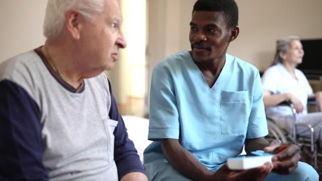 vidéos et rushes de le soignant médical masculin expliquant au patient au sujet du récipient quotidien de pillule - infirmier