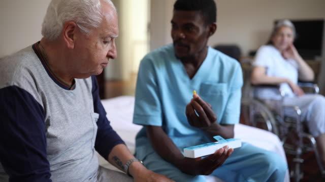vidéos et rushes de le soignant médical masculin parlant avec l'homme aîné au sujet de sa thérapie - chaise roulante