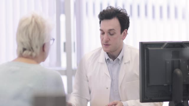 male medical doctor explaining scan results to patient - neurosurgery stock videos & royalty-free footage