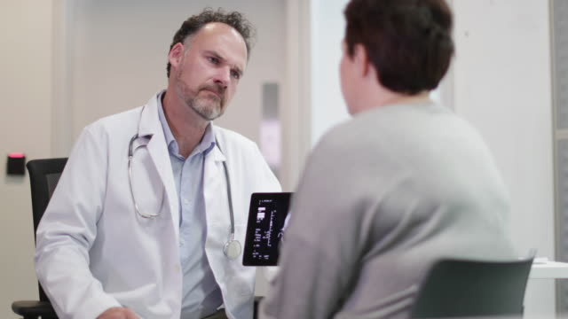 male medical doctor explaining scan results to patient - overweight patient stock videos & royalty-free footage