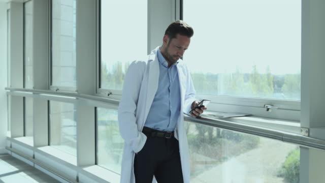 male medical professional using smartphone in corridor - corridoio caratteristica di una costruzione video stock e b–roll