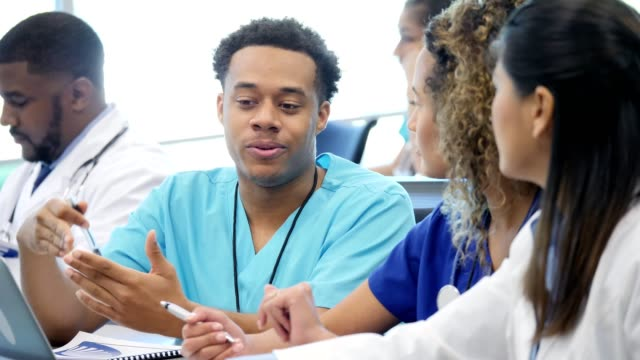 Male medical school student discusses something with classmates before class