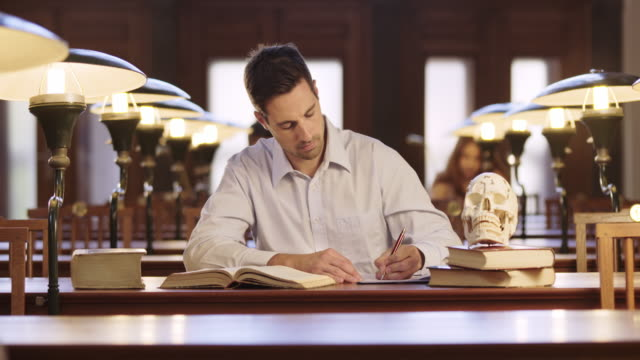 ds male medical student studying with a skull model in the library - medical student stock videos and b-roll footage