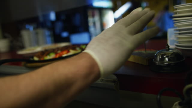 male mexican cook in his thirties places a steaming plate of fajitas in a serving window and rings a bell at a mexican restaurant - protective glove stock videos & royalty-free footage