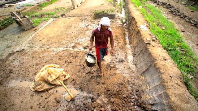 male mixing soil for handmade bricks java indonesia - ziegel stock-videos und b-roll-filmmaterial