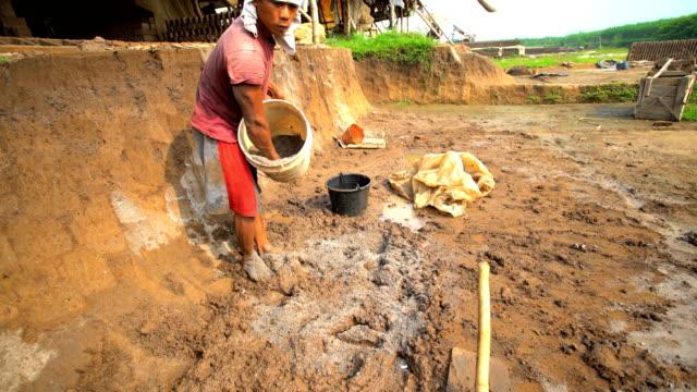 male mixing soil to make handmade bricks java - ziegel stock-videos und b-roll-filmmaterial