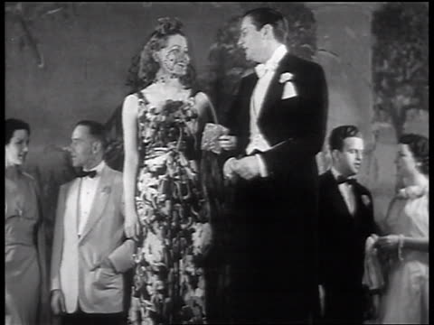 b/w 1937 male model in tails escorting female model with dress + veil / other couples in background - sfilata video stock e b–roll