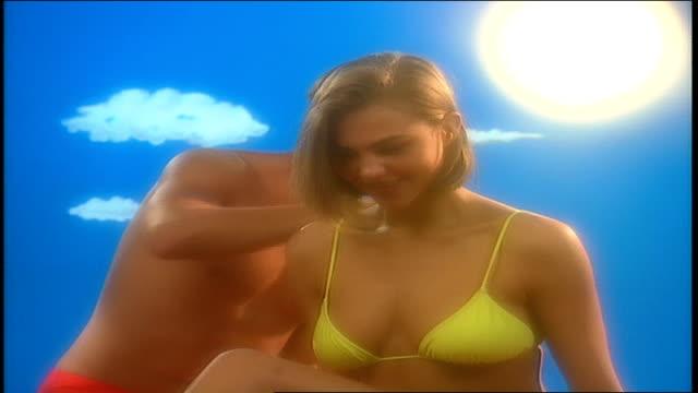 Male Model Rubbing Sun Block on Female Model in Bright Sunny Scene