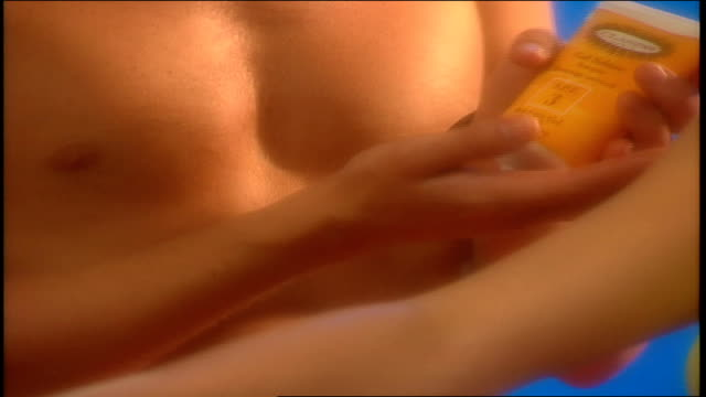 male model rubbing sun block on female models arm in bright sunny scene - sun cream stock videos & royalty-free footage