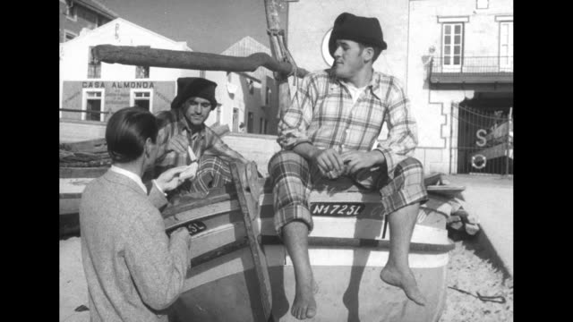 vs male model standing next to fishing boat on beach handing cigarettes to two fisherman sitting on boat / female model wearing top and skirt stands... - hooved animal stock videos and b-roll footage