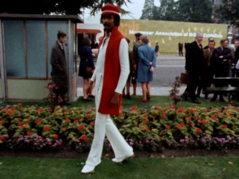 A male model wears a white jump suit with a scarlet midiwaistcoat and matching hat