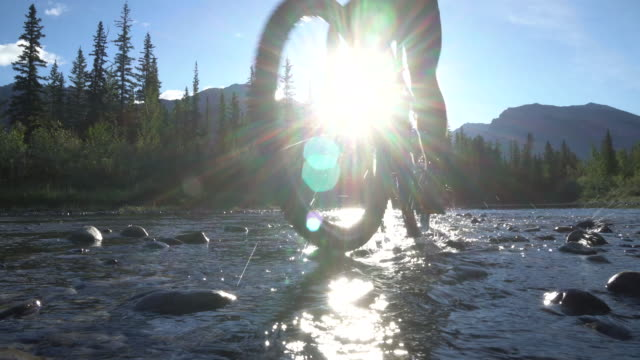 Male mountain bike rider crosses river towards distant mountains