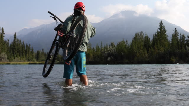 male mountain biker carries bike across fast flowing river - carrying stock videos & royalty-free footage
