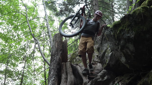 male mountain biker carries bike down steep forest trail - mountain bike stock videos & royalty-free footage