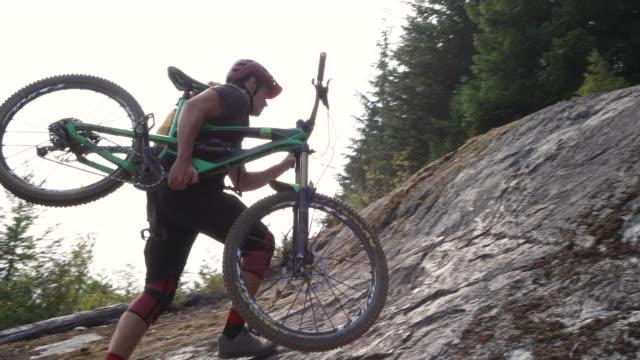 male mountain biker carries bike up steep forest trail - man made object stock videos & royalty-free footage