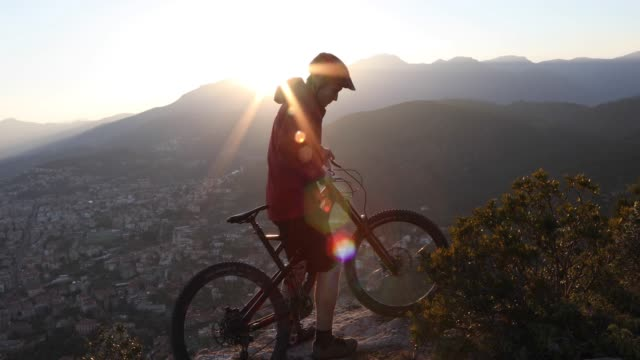 male mountain biker descends rocky slope at sunrise - cycling helmet stock videos & royalty-free footage