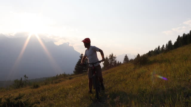 male mountain biker follows trail in high alpine meadow - ヘルメット点の映像素材/bロール