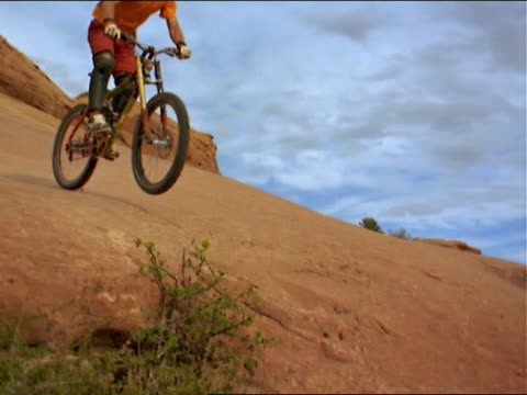 male mountain biker jumps in front of camera in the southwest outdoors - elbow pad stock videos & royalty-free footage