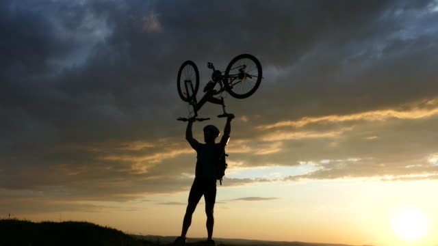 4к male mountain biker lifting up his bike - mountain bike video stock e b–roll