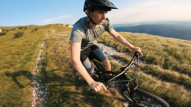 vídeos de stock e filmes b-roll de male mountain biker on bicycle trail moving downhill fast on a beautiful sunny day - cavalgada de lazer