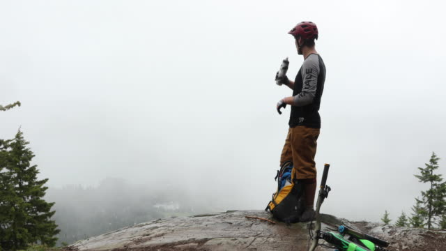 male mountain biker pauses for water in fog - mountain bike stock videos & royalty-free footage