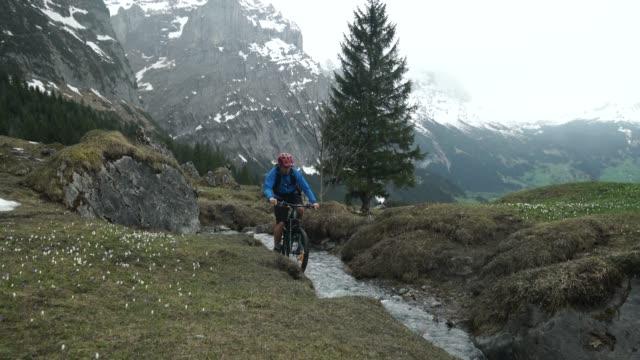 vídeos y material grabado en eventos de stock de pedales de motorista macho de montaña a través de creek en las montañas - one mature man only