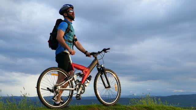 4К mannelijke mountainbiker rusten bovenop