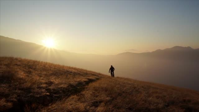 männliche mountainbiker reitet bergweg bei sonnenaufgang - mountainbiking stock-videos und b-roll-filmmaterial