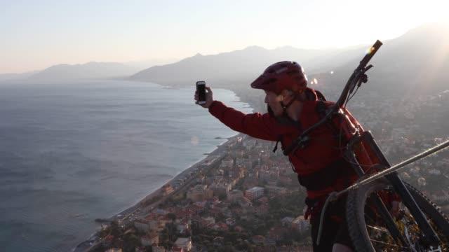 vídeos de stock, filmes e b-roll de o motociclista masculino da montanha toma o pic com telefone esperto no nascer do sol - individualidade