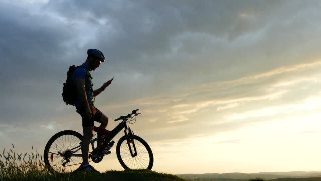 4к male mountain biker using smart phone on top at sunset - on top of stock videos & royalty-free footage