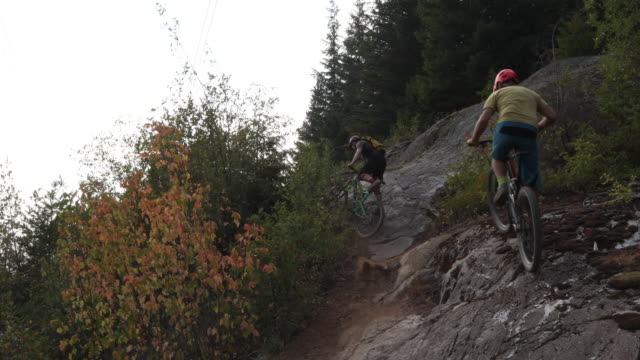 male mountain bikers ride and carry bikes up steep forest trail - trail ride stock videos and b-roll footage