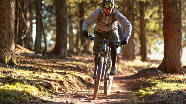 slo mo male mountain bikers riding down a sunny forest trail - nur junge männer stock-videos und b-roll-filmmaterial