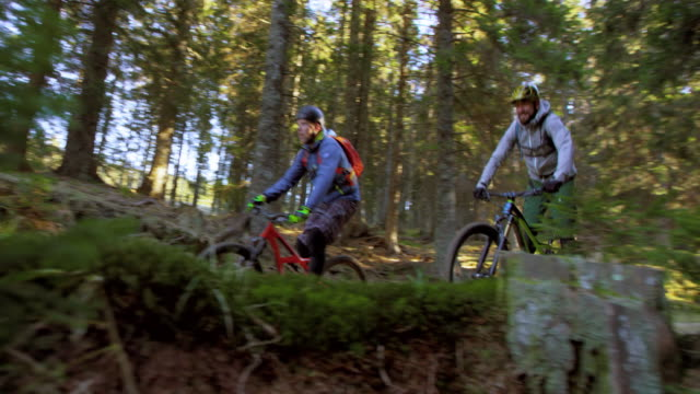 SLO MO Male mountain bikers riding through forest in sunshine